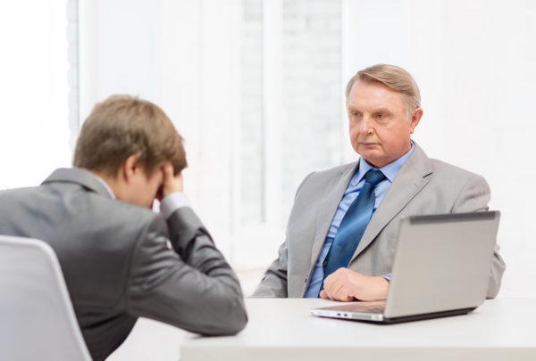 Пожилой мужчина в костюме с осуждением смотрит на молодого парня