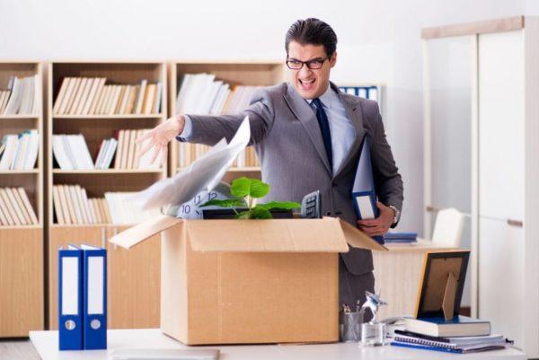 Мужчина в костюме бросает бумаги в коробку на столе