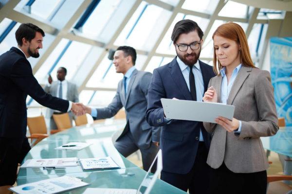 Женщина с документами в руках рядом с мужчиной на фоне офисных сотрудников