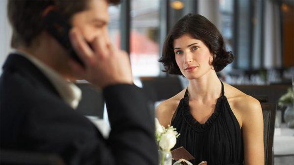 Мужчина говорит по телефону, женщина смотрит на него