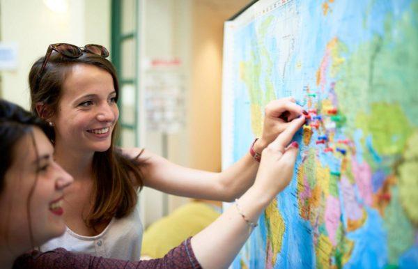 Две девушки ставят магниты на карту