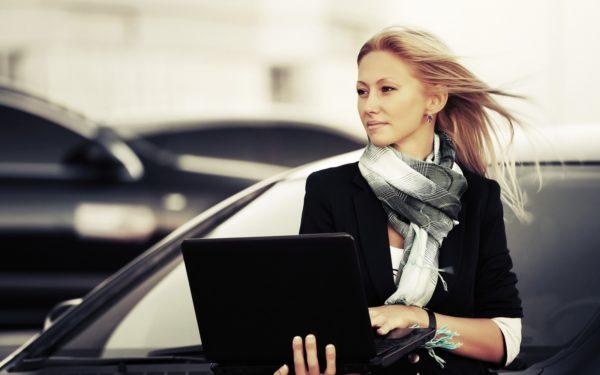 Женщина с ноутбуком у машины