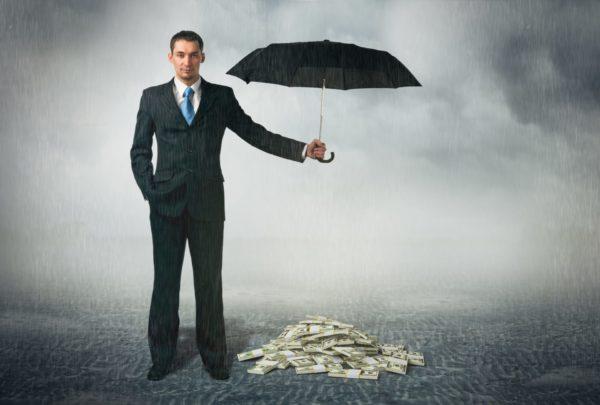 Мужчина держит зонт над кучей денег