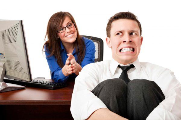 Женщина за столом улыбается, мужчина рядом, обхватив свои колени, корчит гримасу