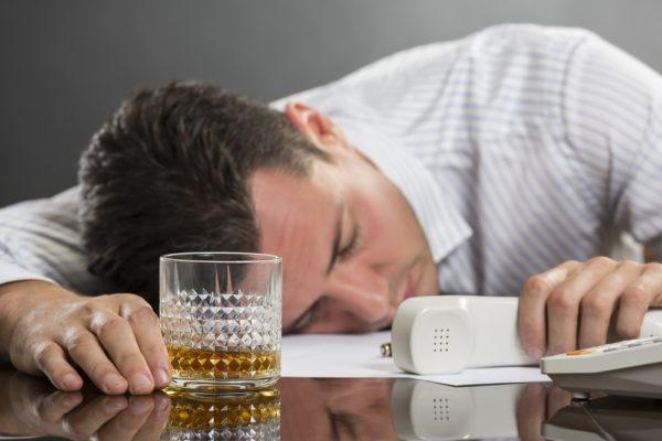 Мужчина с телефонной трубкой в руке и стаканом спит на столе