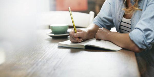 Женщина, сидя за столом, делает записи