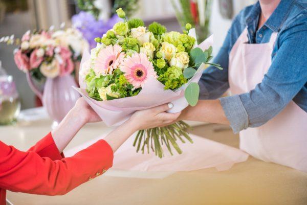 Флорист передаёт букет покупателю